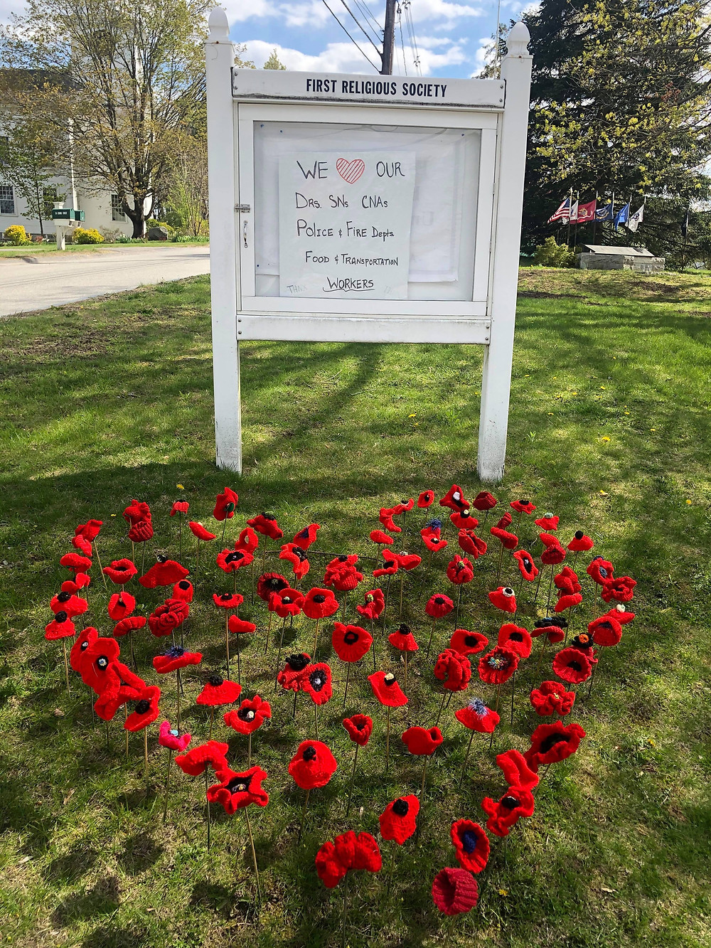 Image of homemade poppies forming a heart beneath a sign that reads We love ourrr Drs, SNs, CNAs, Police & Fire Depts, Food & Transportation Workers