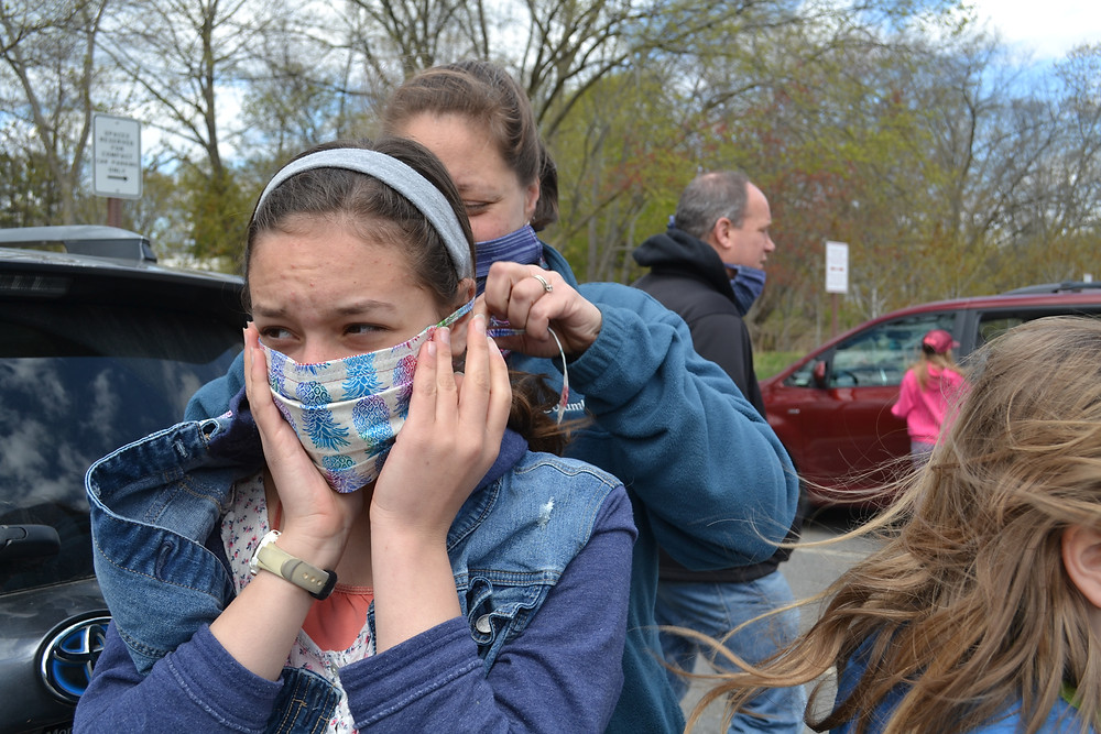 Girl trying to put a mask on another girl before a socially distanced birthday celebration.