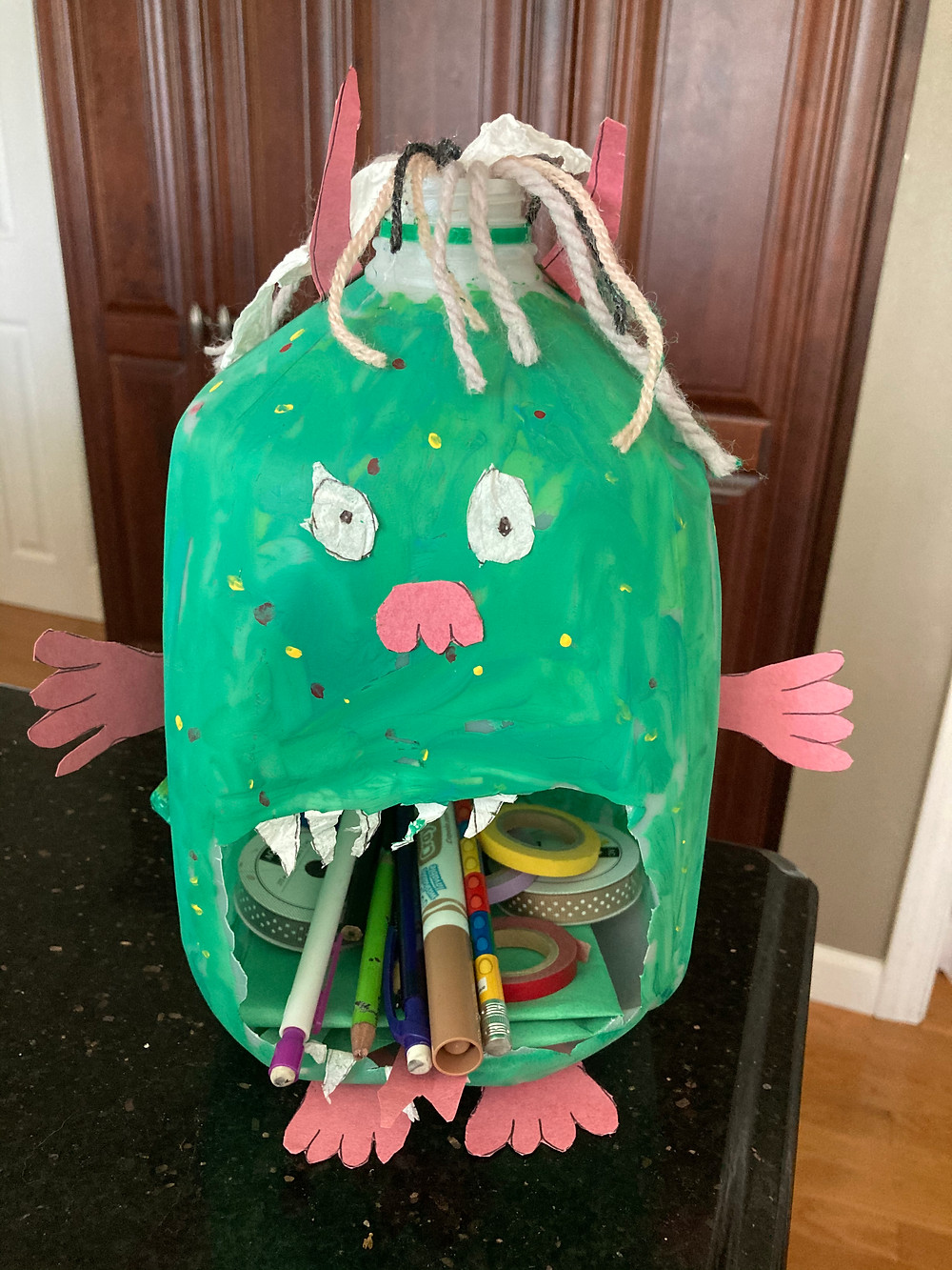 Plastic milk jug painted green with large eyes and mouth cut out to hold school supplies.