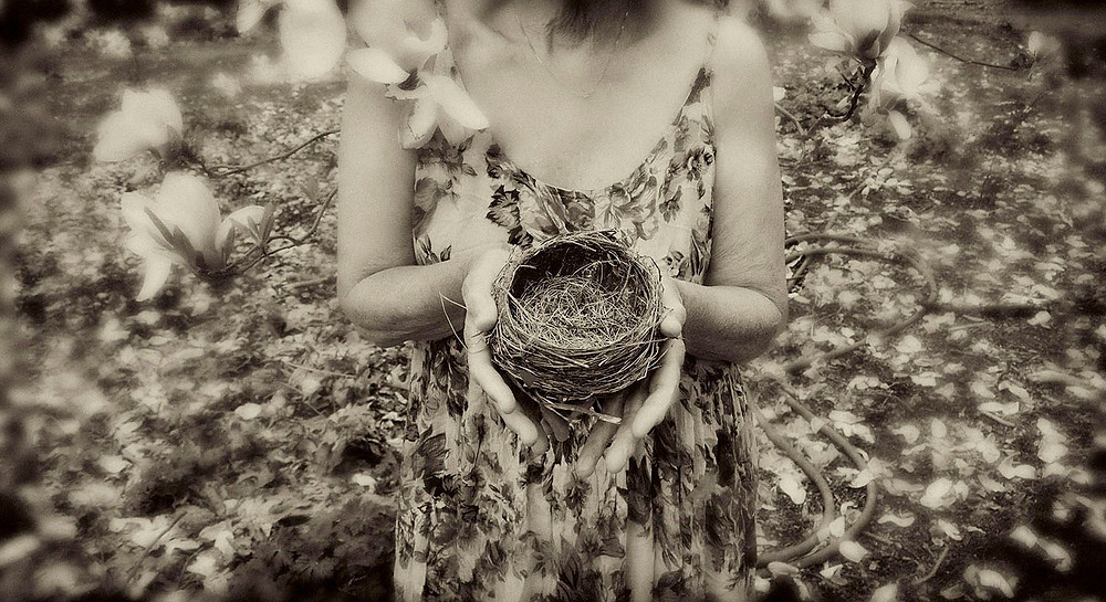 Sepia image of a woman holding an empty bird's nest.