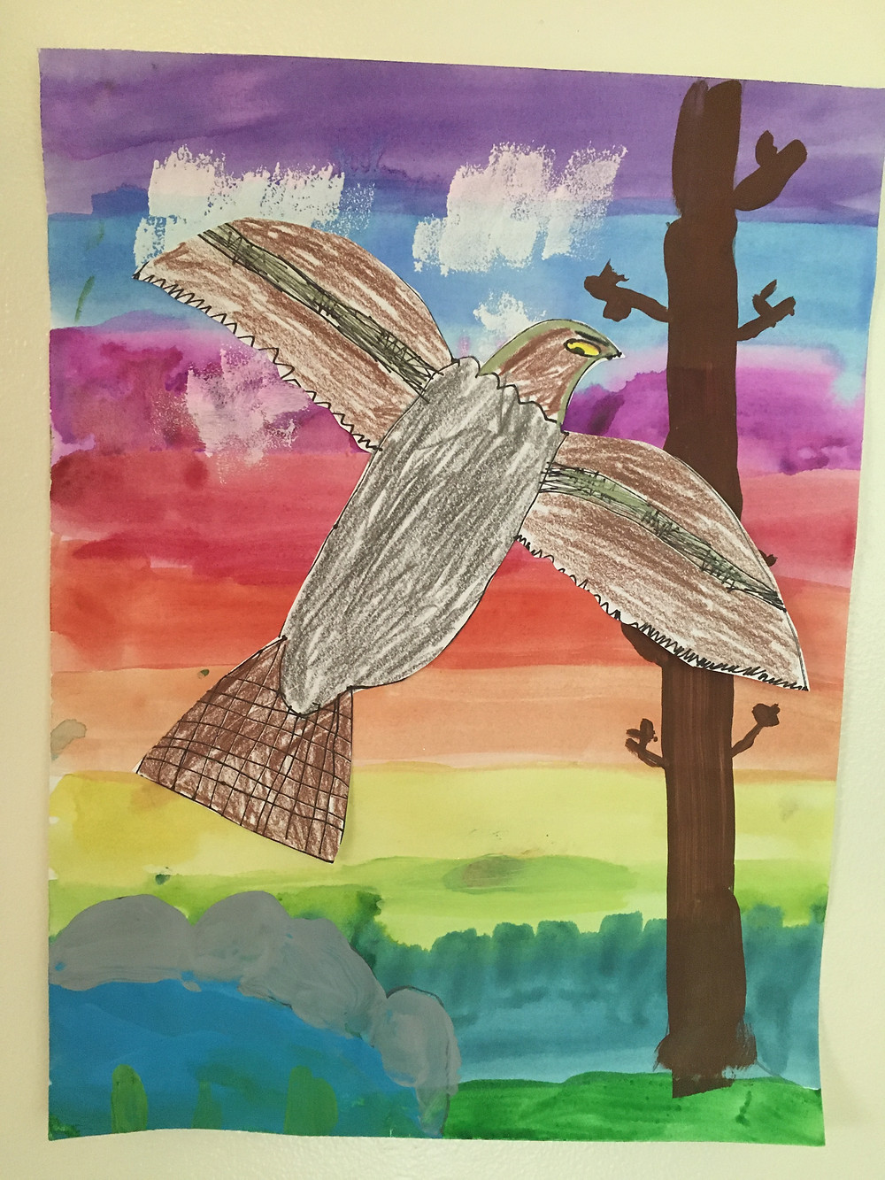 Mixed media drawing of a falcon over a bright rainbow sky background.