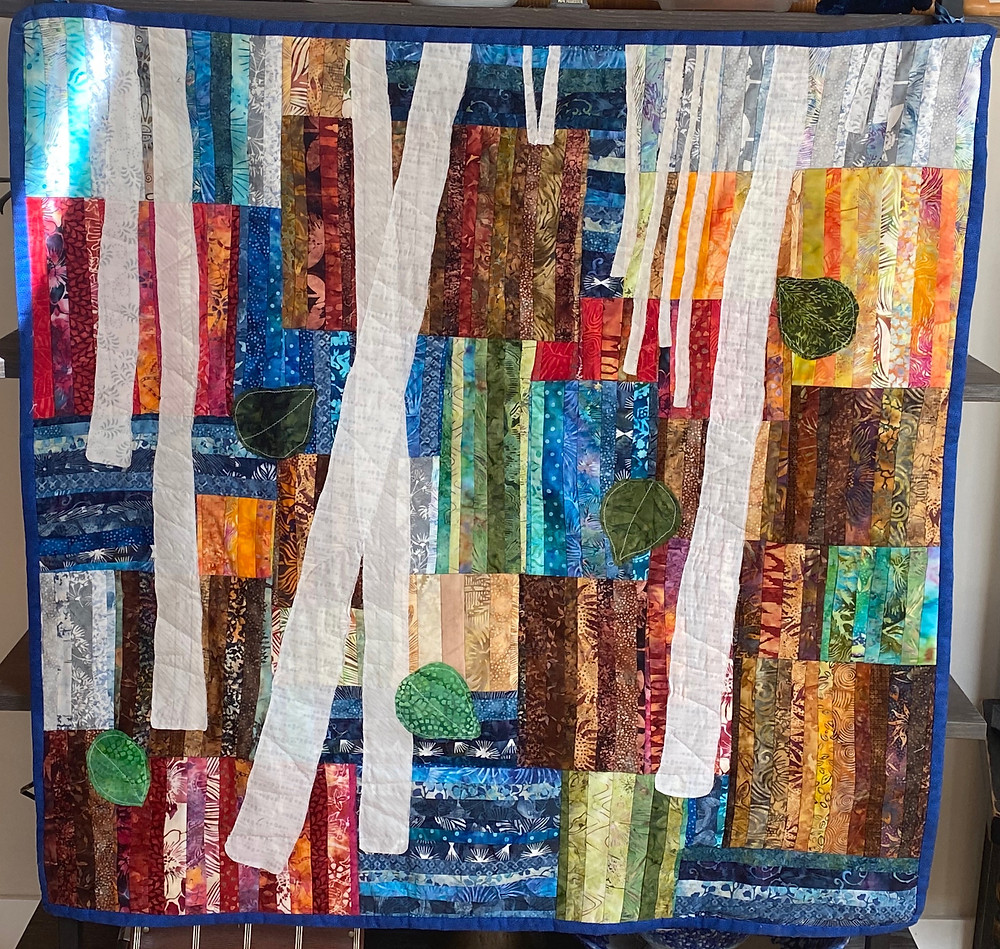 Quilted wall hanging featuring abstract birch tree design on colorful block layout.