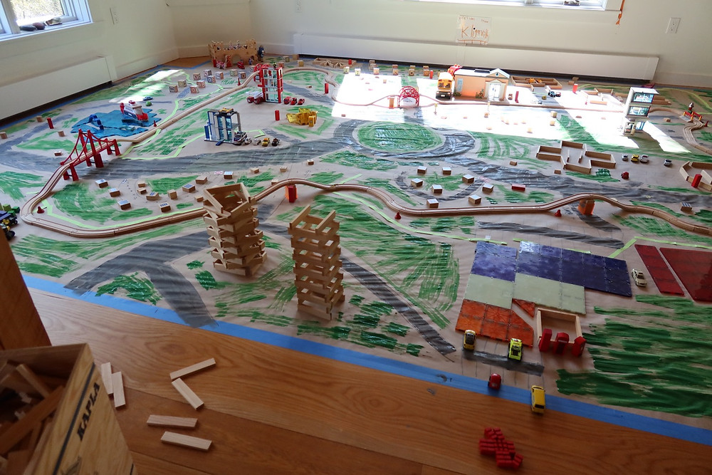Drawing of pretend city overlaid with train tracks and buildings designed for indoor play.