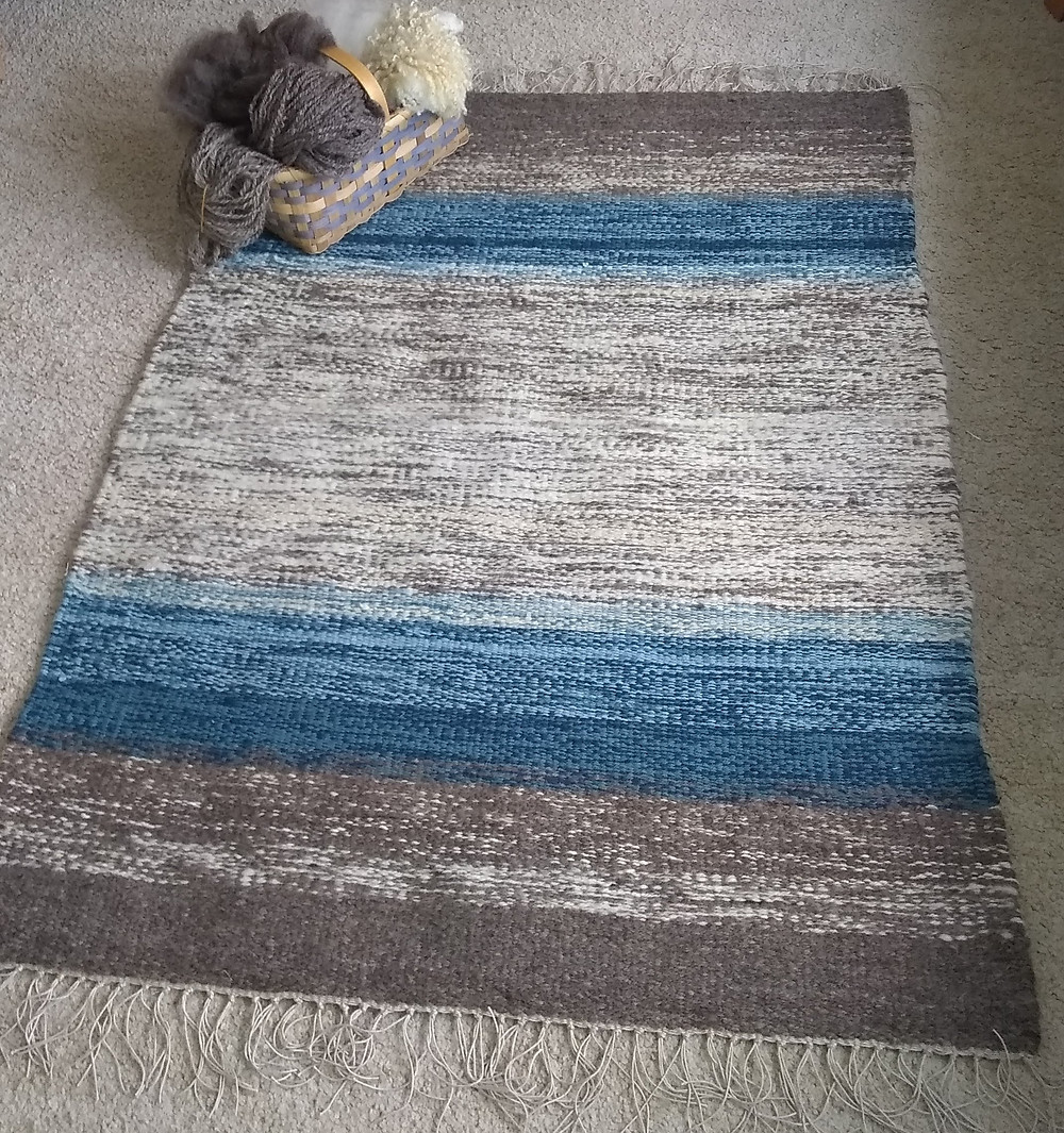 Gray, white and blue handwoven rug with fringe.