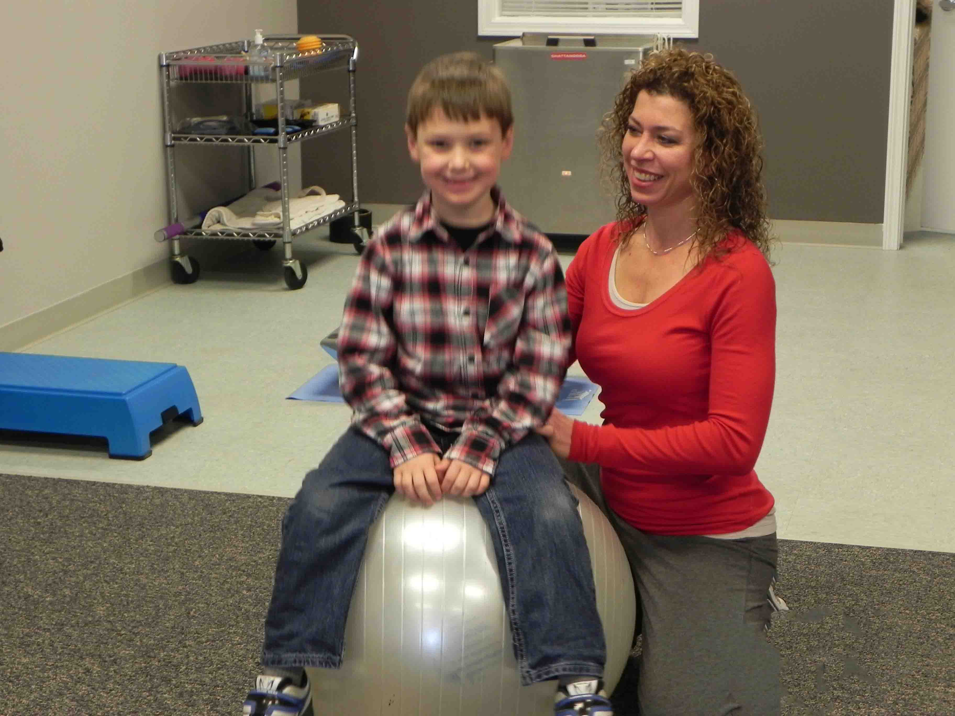 Child with physical therapist on a ball