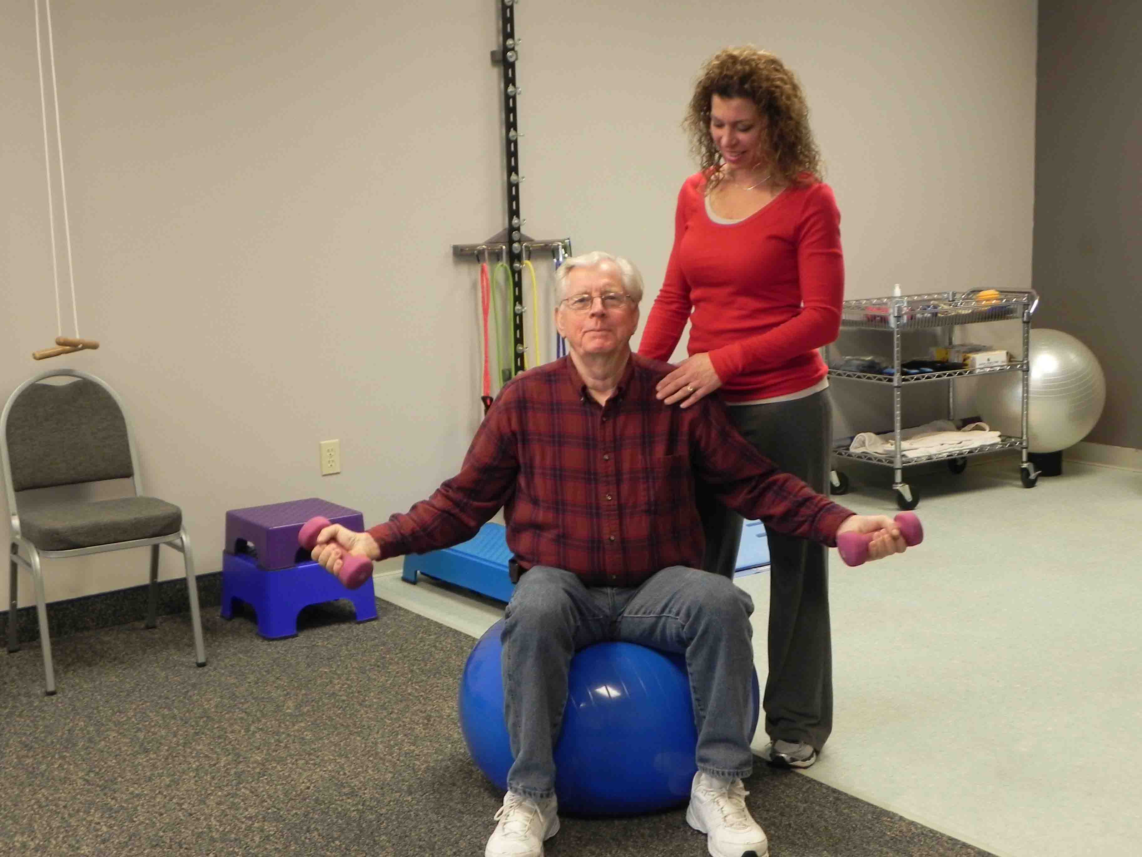 Senior with Physical therapist sitting on a exercise ball