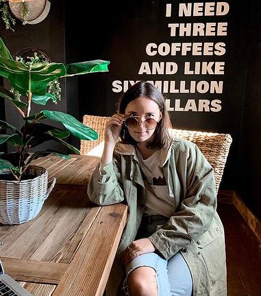 employee sarah sitting at table looking at camera half way lowering glasses wearing a green jacket