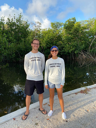 founders gaby and brendan standing next to each other outside with a backdrop of mangroves.