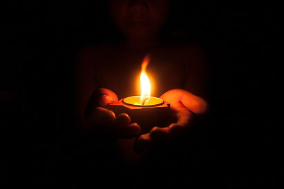Little child holding burning candle in d