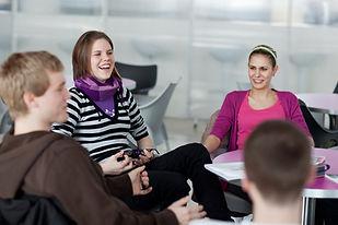 des jeunes adultes discutent et rient en classe