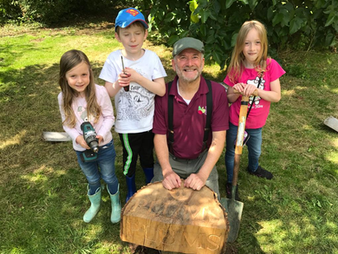 A group of volunteers with a carved stool in Trotshill Community Orchard
