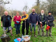 A group of volunteers clearing brambles in Trotshill Community Orchard