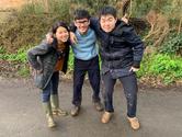Three young very muddy adult volunteers