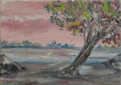 Scenery of a lake by the shore with a tree with colourful leaves