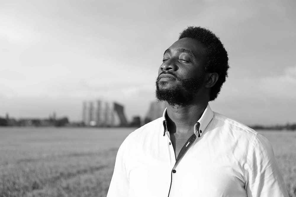 Tolulope Olajide stands in the middle of the field with his eyes closed and head raised. Balanced Wheel | BW