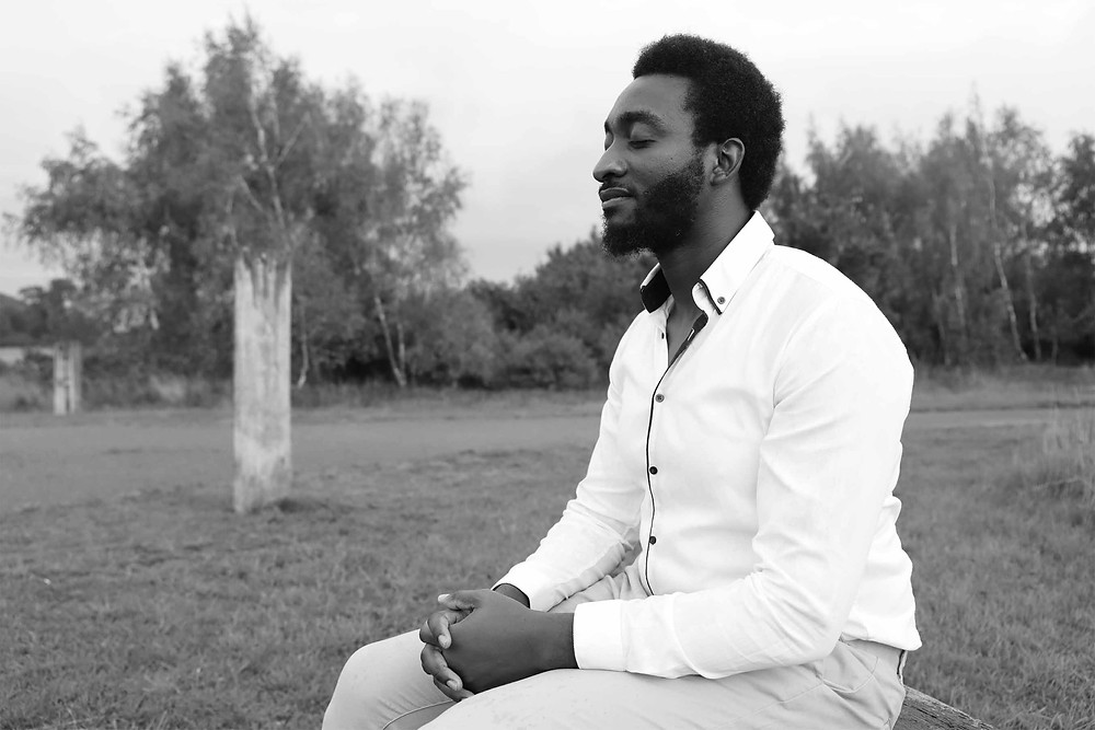 Coping with guilt and grief, Tolu Olajide siting on a bench in the woodland | Balanced Wheel | BW