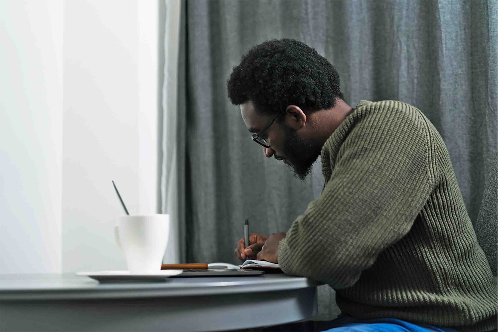 Tolulope Olajide sat at a table writing | Balanced Wheel | How to reach out to somone grieving blog post