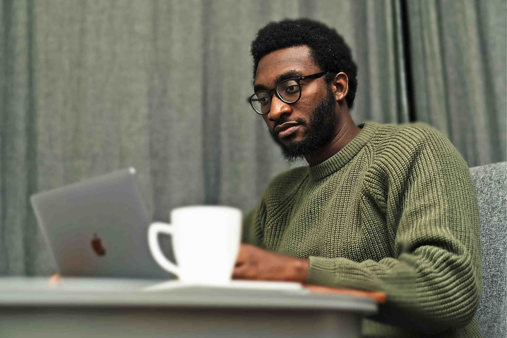 Tolu in a green jumper sitting at a table with his laptop | Using Music to cope with grief | Balanced Wheel
