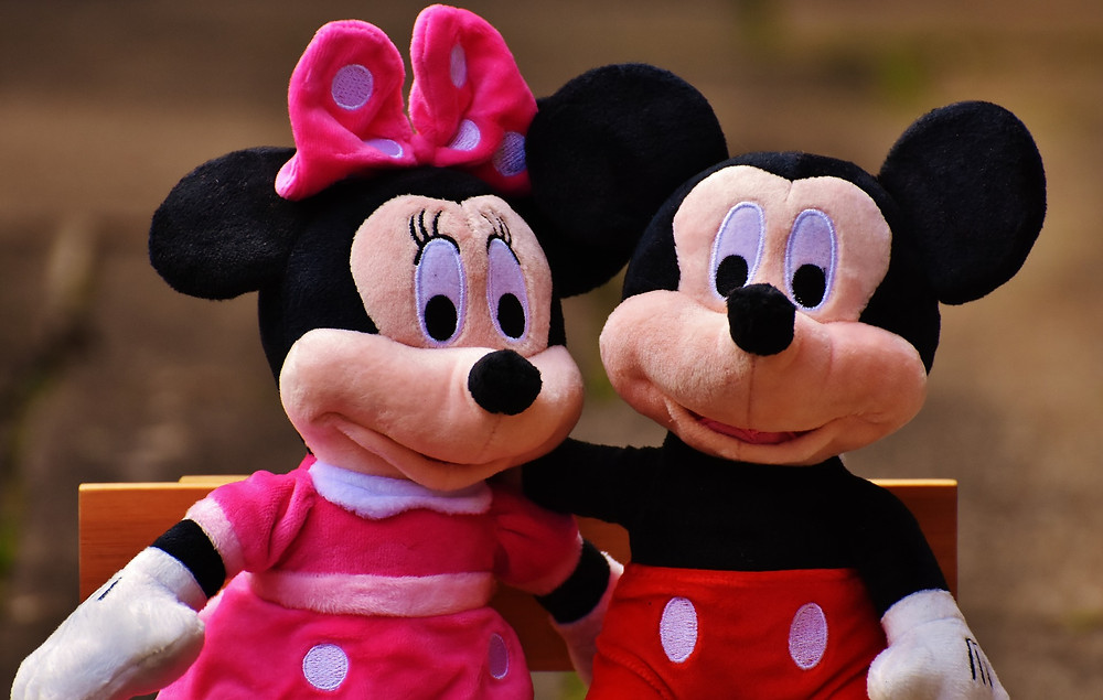 Mickey Mouse and Minnie Mouse sitting on a bench