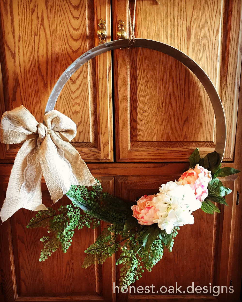 metal ring with fake flowers, greenery and a burlap bow attached