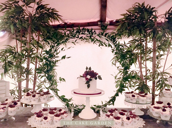 Single tier wedding cake and cupcakes with foliage hoop frame