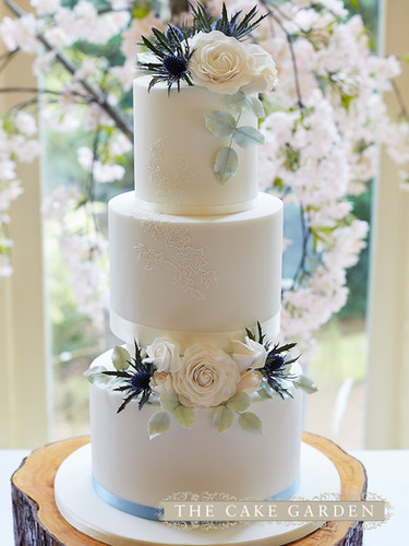 3 tier elevated iced cake with suagr flowers