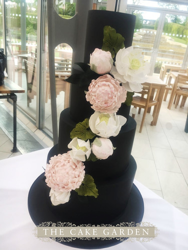 Black iced cake with sugar peonies and waterlilies
