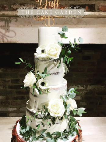 4 tier semi skimmed with rustic whites and green foliage