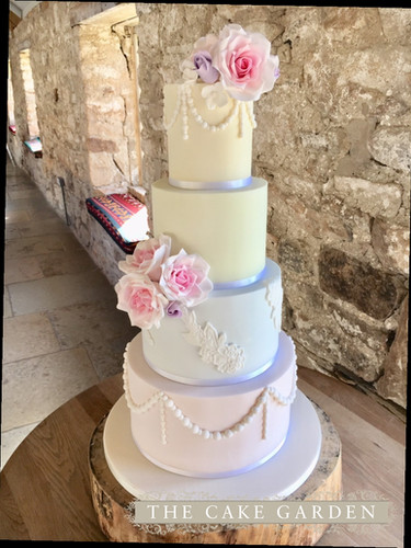 4 colour pastels with lace, pearls and sugar roses.