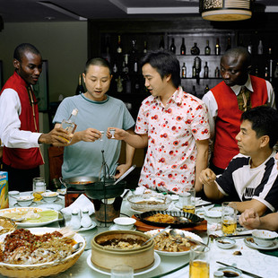 """A celebratory dinner for the meeting of the association of the Chinese entrepreneurs of Lagos that takes place monthly at the restaurant """"Mr. Chang"""". The members of the association are the new generation of Chinese businessmen in Africa. They are often very young and their companies are booming. The waiters are dressed in Chinese costumes directly imported."""