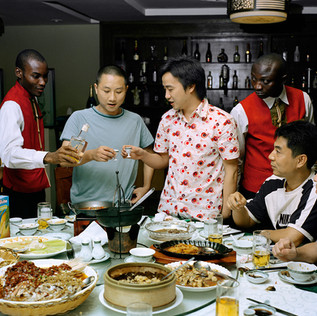 "A celebratory dinner for the meeting of the association of the Chinese entrepreneurs of Lagos that takes place monthly at the restaurant ""Mr. Chang"". The members of the association are the new generation of Chinese businessmen in Africa. They are often very young and their companies are booming. The waiters are dressed in Chinese costumes directly imported."