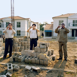 Two Chinese employees of the Chinese company WIETC and their Congolese translator are photographing the Bagongo site where WIETC is constructing 40 villas at the place of hundreds of shacks that have been demolished. The photos will be used in China to show the progress of the work and to attract new Chinese investments. The undeclared objective of the Bacongo project is to substitute part of the population of the neighbourhood, famous for being a stronghold of the Ninjas rebels that have fought here some of the most dramatic battles of the civil war (1997-2001).