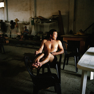 A worker of Guangxi Hydropower Construction Company rests on his day off in the warehouse that also doubles as his very rudimental living quarters.