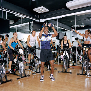 A six a.m. spinning class at Ultimate Fitness. In a white T-shirt, the vice president of Access Haiti, one of the country's major Internet providers. With her hands in the air, Claudie Marsan, a prominent corporate lawyer. Pétion-Ville. Haiti