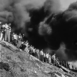 A crowd watches a fire caused by the sabotage of an oil pipeline.