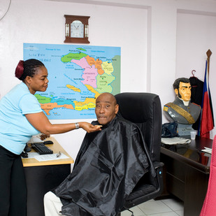 Julio Jean Pierre is a host on Télévision Nationale d'Haïti (TNH). He's being made up a few minutes before going on air. Behind him, a bust of Alexandre Pétion, president of the Haitian Republic from 1806 until his death in 1818, one of the fathers of the nation. Port-au-Prince. Haiti, 2012