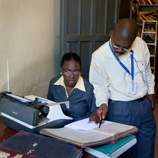 A secretary from the Direction Générale des Impôts (Tax Office) copies out land acquisition deeds from the 19th century on a typewriter. Port-au-Prince. Haiti