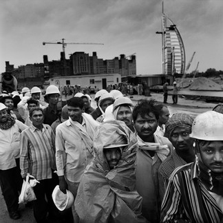 A group of Pakistani workers wait for a bus after their day's work on one of the many building sites facing the sea. Artificial islands, designed to combat the 'shortage of beaches', are built here. Behind them is the Burj al-Arab hotel, an architectural folly giving the measure of this city in perpetual motion.