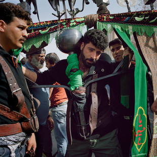 In an exercise that is half athletic and half religious, the strong man from the holy city of Qom show their force and faith carrying for as long as they can a over 100kg yoke for the religious festivity of Arba'een that commemorates the decapitation of the Imam Hossein, which occurred in the year 860 AD. Iran, Qom, February 2009.