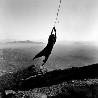 One of the hills overlooking Kabul, where a boy swings from the dangling wires of a pylon destroyed by the war.