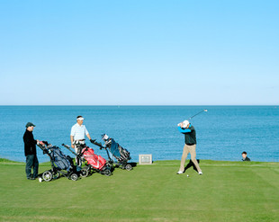 """Players at the Royal Jersey Golf Club. Jersey is the most southerly of the Channel Islands and has the best sunshine record in the British Isles. That has attracted many tourists over the years, but today many English people who come to the Island are not there for the sun. As Jersey Finance, the body representing Jersey's top-grossing industry, acknowledges, """"For many corporate treasurers, institutional bankers and treasury specialists, fund promoters, brokers and other corporate financiers, Jersey represents an extension of the City of London.""""  Although the bulk of Jersey's business comes from Britain, businesses in Jersey are not subject to the same regulations and often engage in aggressive tax avoidance practices. Jersey."""