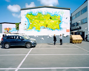 In downtown St. Helier, a mural depicts a stylized map of the Island of Jersey. The main industries used to be tourism and agriculture. However, the offshore financial sector has taken over and today Jersey warehouses nearly $2 trillion of the world's wealth. 42 banking groups are present on this island of only 8 x 15 km. Jersey