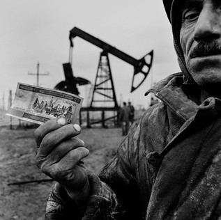 On the oldest oil field of the Caspian a worker displays a Manat note (Azeri currency). The drawing of Bibi Heybat on the note is more than a century old, of when Baku was the world capital of black gold. The workmen are paid 60 dollars a month and they survive with help from exiled cousins in Russia. The same work, when done for BP, is paid 500 dollars.