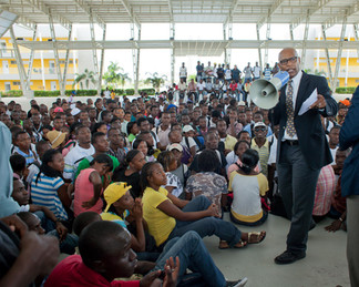 The Université Roi Henri Christophe. Its president Jean-Marie Théodat tries to end a student strike on the new campus financed and built by the Dominican Republic. He is announcing the different courses of study that the nearly 2,000 students have been awaiting for months. Limonade.