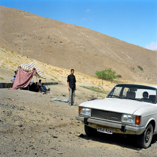 Vahid, 15, is a Kurd from Zanjan, a city in the north east of Iran. He is photographed here in the mountains south of Rasht. On Fridays his family drive into the hills to escape the heat and to picnic. Their car is a Paykan, whose design is modeled on the British made Hillman Hunter of the 1960's and 70's. The gas-guzzling make was discontinued in 2005 after 30 years of production. Paykans have been the butt of endless jokes over the years (What do you find on the last pages of a Paykan owner's manual? The bus schedule) but despite its shortcomings, the Paykan is the car you are most likely to find on a Friday parked on a mountainside beside an improbably large group of picnickers. Iran, Tehran, August 2006.