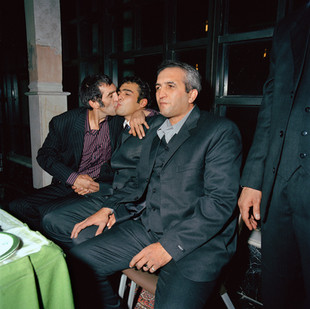 The artist Khosrow Hassanzadeh hugs his nephew Mostapha, who has just married Zeinab Fazali. Seated in the first row is Sedegh Ali, the father of the bride. This celebration is a mix of tradition and modernity. Men and women are segregated, but everyone will later be able to watch the videos from the opposite side made with video cameras or mobile phones. The Hassanzadeh family are fruit sellers in the traditional quarters of southern Tehran, but have rented a reception hall for the wedding in north Tehran's smartest neighborhood. The wedding was arranged by the parents, who introduced the bride and groom, and negotiated the terms of the contract, but both sides emphasize that the most important element of any marriage is love. Iran, Tehran, December 2006.