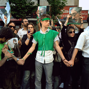 """A young man, dressed in the green colors of the Iranian reformist movement, tries to hold back the crowd that came to protest the results of the president election held two days earlier. When president Ahmadinejad has been announced winner with a 62% score the fury has been stronger then the fear. Tens of thousands Iranians have taken to the streets shouting """"where is my vote"""" and braving the Basij, the teargas and the arrests. These have been the biggest non-authorized rallies since the 1979 Islamic revolution.  Avenue Vali-Asr, Tehran, June 2009."""
