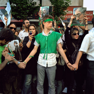 "A young man, dressed in the green colors of the Iranian reformist movement, tries to hold back the crowd that came to protest the results of the president election held two days earlier. When president Ahmadinejad has been announced winner with a 62% score the fury has been stronger then the fear. Tens of thousands Iranians have taken to the streets shouting ""where is my vote"" and braving the Basij, the teargas and the arrests. These have been the biggest non-authorized rallies since the 1979 Islamic revolution.  Avenue Vali-Asr, Tehran, June 2009."