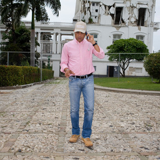 "Michel Joseph Martelly in front of the presidential palace destroyed by the January 12, 2010, earthquake. The word ""Prezidan"" is written on his cap in Creole. Port-au-Prince. Haiti, 2012"