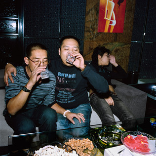 "Xiang Yang Yé, (on the left), known as Philippe, at the Trust-Mart Vegas KTV karaoke in Wenzhou, his hometown. He is celebrating with a childhood friend his brief Chinese vacation. Philippe lives in Africa where he has not become rich yet but has made ""just a few million dollars"" as he says. In Congo, Philippe and his 80 member strong family, are active in almost all areas: restaurants, nightclubs, retail, construction materials, cement import and precious wood export. While in China he is recruiting skilled workers for the launch of three new businesses in Congo: car spare parts import, a furniture plant and a cigarette factory."